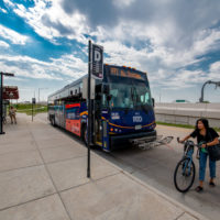 Woman walks away from bus with bike