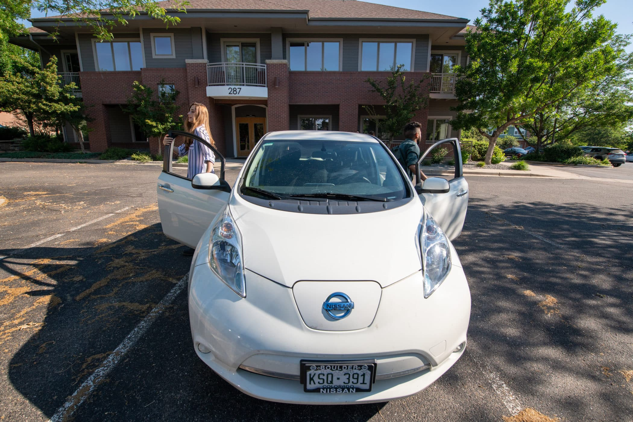 Two people get out of their electric vehicle